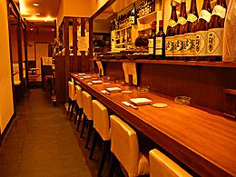 入り口すぐにあるカウンターには、おばんざいの大皿とお酒がずらり。調理の様子もよく見えます。